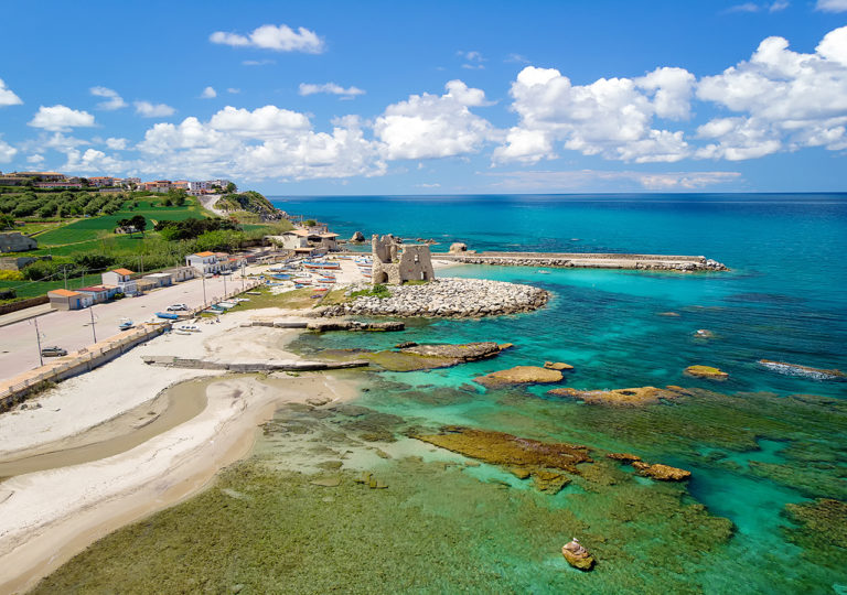 Fishing italian village Briatico in Calabria with turquoise sea and old saracen tower. Drone Panorama - Italy
