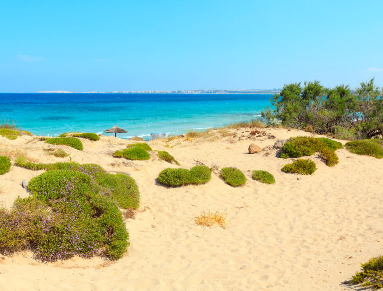 Picturesque Ionian sea beach Punta della Suina, Salento, Puglia, Italy. Gallipoli town view in far.